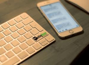 campagnes sms logo imprimé sur shift droit d'un clavier mac iphone en perspective sur bureau bambou